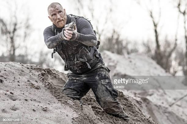 Macho geschoren redhead mannelijke militaire swat beveiliging anti-terreur lid geleid tijdens de training in modderige buiten instelling