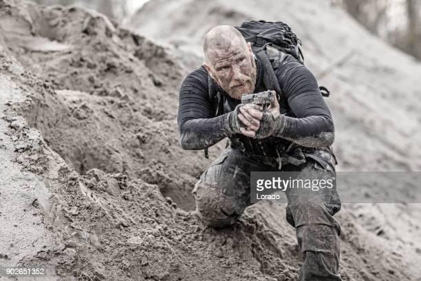 Macho rasiert leitete Rothaarige männliche militärische Swat Sicherheit anti-Terror-Mitglied während des Trainings in schlammigen outdoor-Ambiente