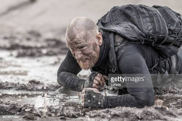 macho shaven headed redhead male military swat security anti terror member during training in muddy outdoor setting - army training stock pictures, royalty-free photos & images