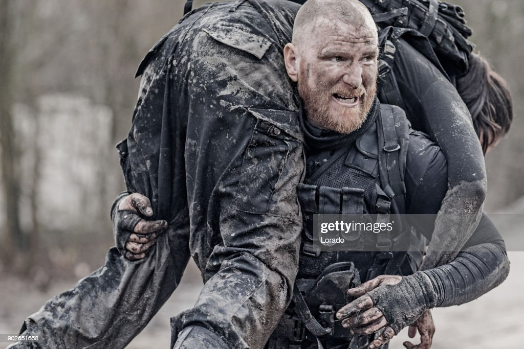 Macho shaven headed redhead male military swat security anti terror member carrying female team member during operations : Stock Photo