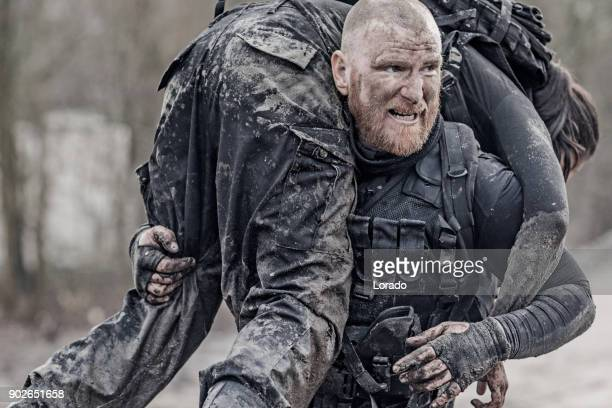 Macho shaven headed redhead male military swat security anti terror member carrying female team member during operations