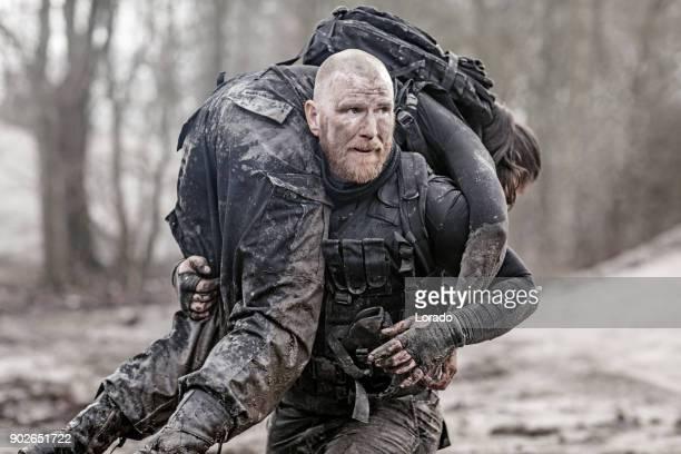 macho geschoren hoofd roodharige mannelijke militaire swat beveiliging anti-terreur lid uitvoering van vrouwelijke teamlid tijdens operaties - redding sporten stockfoto's en -beelden