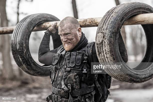 macho shaven headed redhead male military swat security anti terror member during training in muddy outdoor setting - military training stock pictures, royalty-free photos & images