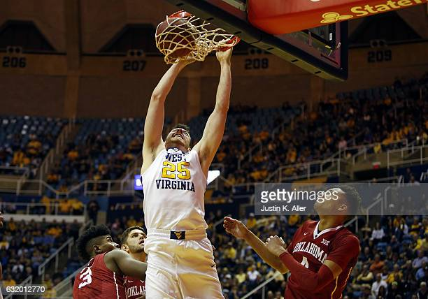 Maciej Bender of the West Virginia Mountaineers dunks against Jamuni McNeace of the Oklahoma Sooners at the WVU Coliseum on January 18 2017 in...