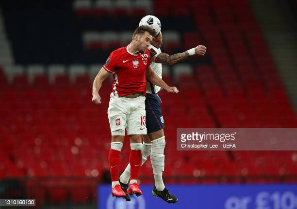 Maciej Rybus of Poland competes for a header with Kyle Walker of England during the FIFA World Cup 2022 Qatar qualifying match between England and...