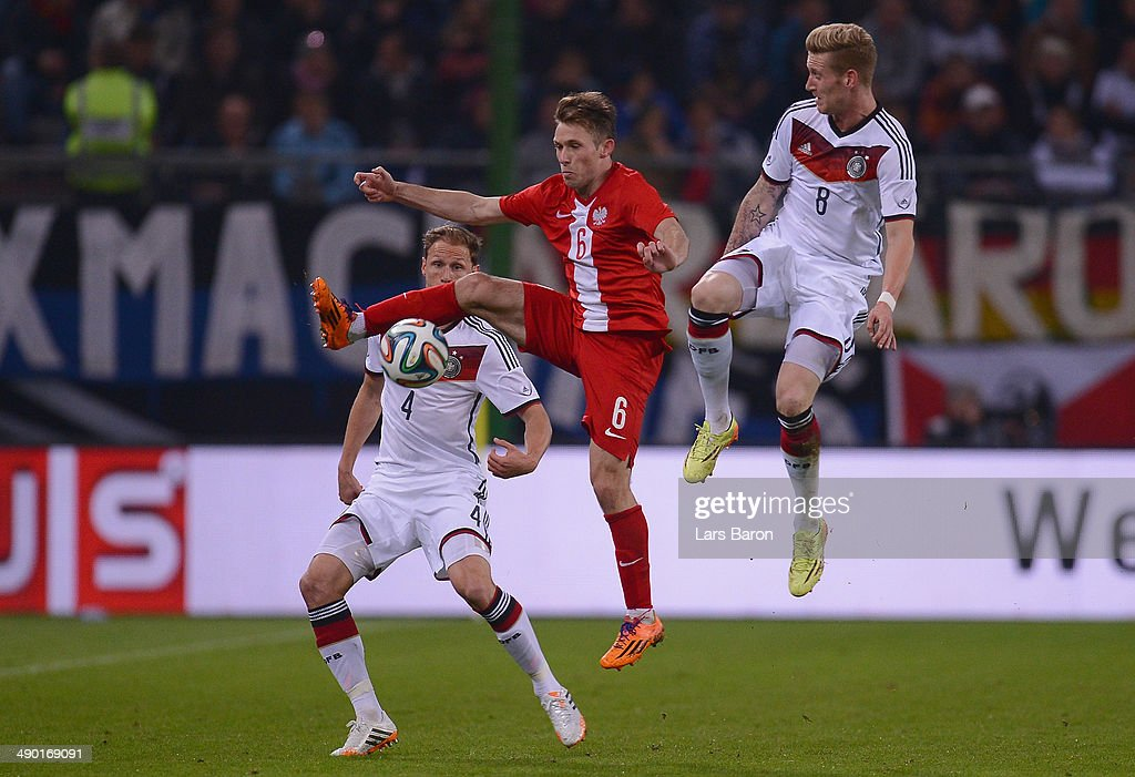 Maciej Rybus pf Poland is challenged by Benedikt Hoewedes and Andre Hahn of Germany during the International Friendly match between Germany and Poland at Imtech Arena on May 13, 2014 in Hamburg, Germany.