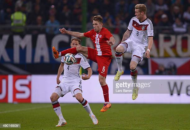 Maciej Rybus pf Poland is challenged by Benedikt Hoewedes and Andre Hahn of Germany during the International Friendly match between Germany and...