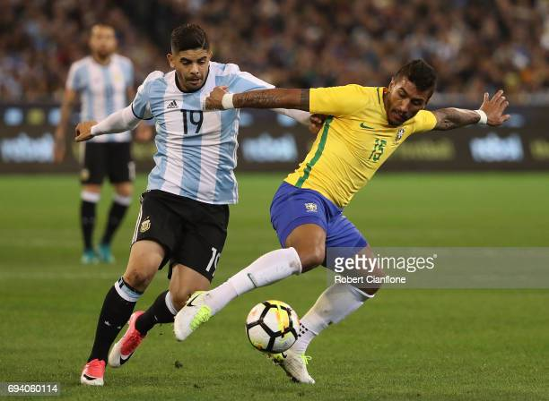 Maciel Junior of Brazil is challenged by Ever Banega of Argentina during the Brazil Global Tour match between Brazil and Argentina at Melbourne...