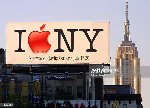 Macintosh billboard announcing the upcoming 2001 Macworld Conference and Expo stands in front of the Empire State Building July 11, 2001 in New York...
