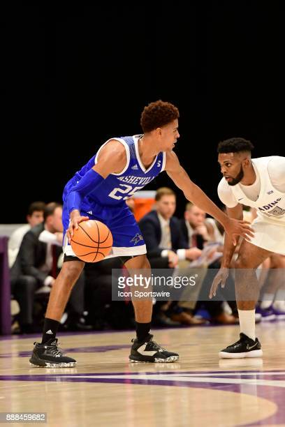 MaCio Teague guard UNC Asheville Bulldogs dribbles the basketball downcourt against Devin Sibley guard Furman University Paladins Tuesday December 5...