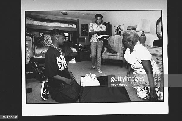 Mack Daddy member of rap duo Kris Kross kneeling on floor in front of open suitcase as his mom Donna brings him clothes to pack for his current...