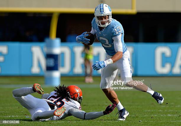 Mack Hollins of the North Carolina Tar Heel avoids Maurice Canady of the Virginia Cavaliers during their game at Kenan Stadium on October 24 2015 in...
