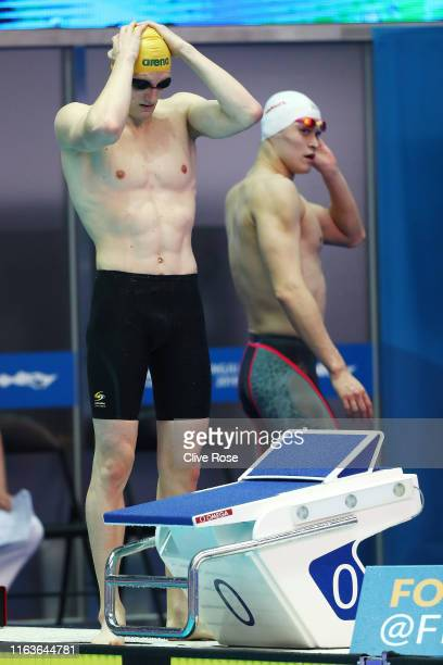 Mack Horton of Australia prepares to compete in the Men's 800m Freestyle heats as Sun Yang of China exits the pool deck on day three of the Gwangju...