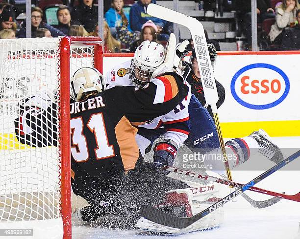 Mack Shields of the Calgary Hitmen gets knocked down by Taylor Cooper of the Regina Pats during a WHL game at Scotiabank Saddledome on November 27...