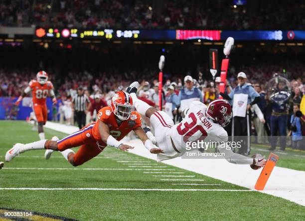 Mack Wilson of the Alabama Crimson Tide scores a touchdown on an interception as Kelly Bryant of the Clemson Tigers defends in the second half of the...