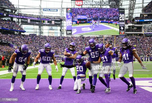 Mackensie Alexander of the Minnesota Vikings celebrates with teammates after intercepting the ball in the fourth quarter of the game against the...