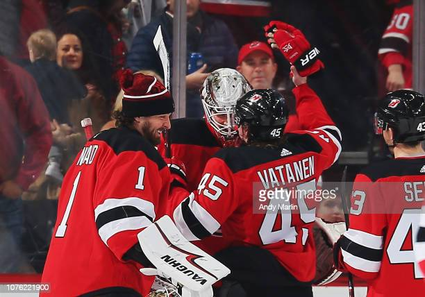 Mackenzie Blackwood of the New Jersey Devils is congratulated by Keith Kinkaid and Sami Vatanen after defeating the Vancouver Canucks at Prudential...