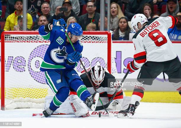 Mackenzie Blackwood of the New Jersey Devils looks on as teammates Will Butcher battles Sven Baertschi of the Vancouver Canucks for a loose puck...