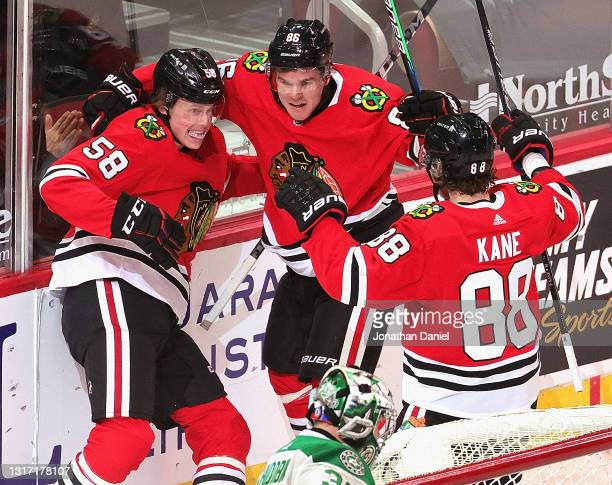 MacKenzie Entwistle of the Chicago Blackhawks celebrates his first career NHL goal in the first period with Mike Hardman and Patrick Kane against...