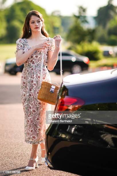 Mackenzie Foy wears earrings, a floral print dress, a basket bag, white shoes, outside Miu Miu Club 2020, on June 29, 2019 in Paris, France.