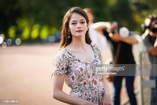 Mackenzie Foy wears earrings, a floral print dress, outside Miu Miu Club 2020, on June 29, 2019 in Paris, France.