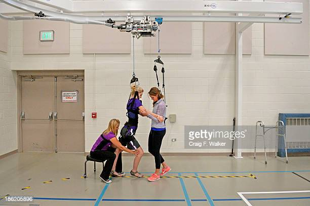 Mackenzie Gorden works with therapists Emma Dawson left and Shelby Allen on a weightsupport walking track wearing a a pair of dress shoes at Craig...