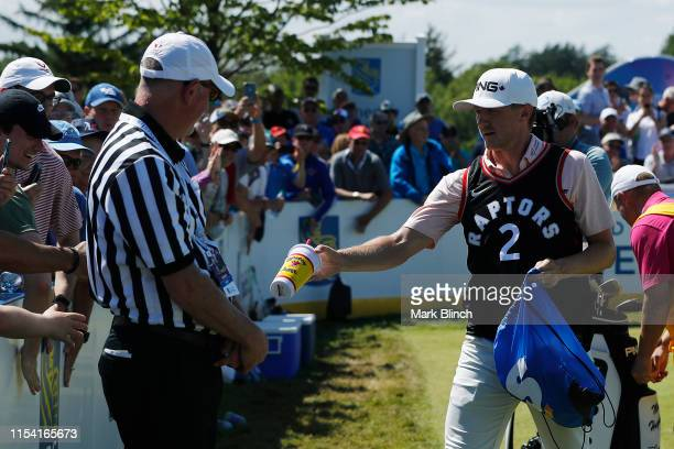 Mackenzie Hughes of Canada hands out giveaways into the stands on the 13th hole during the first round of the RBC Canadian Open at Hamilton Golf and...