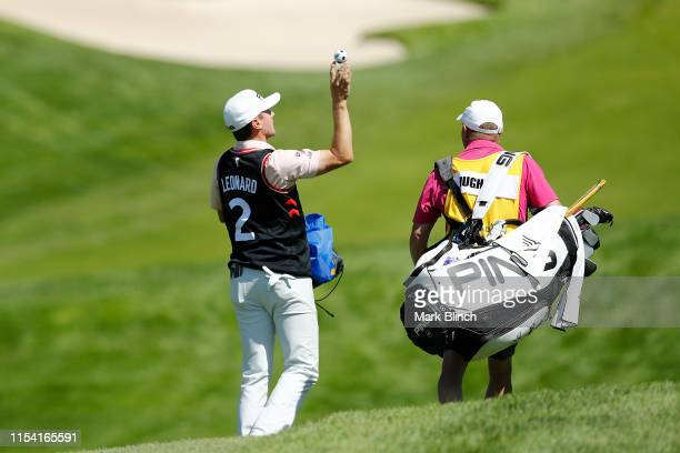 Mackenzie Hughes of Canada throws giveaways into the stands on the 13th hole during the first round of the RBC Canadian Open at Hamilton Golf and...