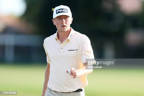 MacKenzie Hughes of Canada waves to the gallery after a putt on the 14th hole during the Honda Classic at PGA National Resort and Spa Champion course...