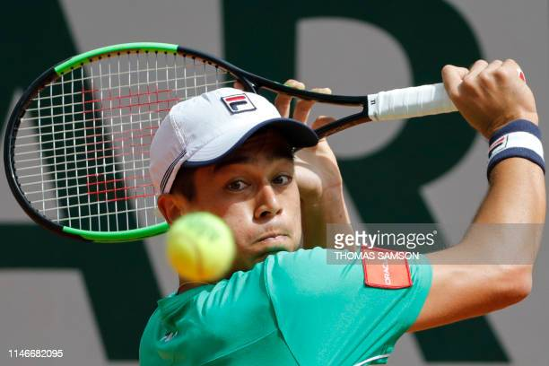 Mackenzie McDonald of the US returns the ball to Japan's Yoshihito Nishiok during their men's singles first round match on day three of The Roland...