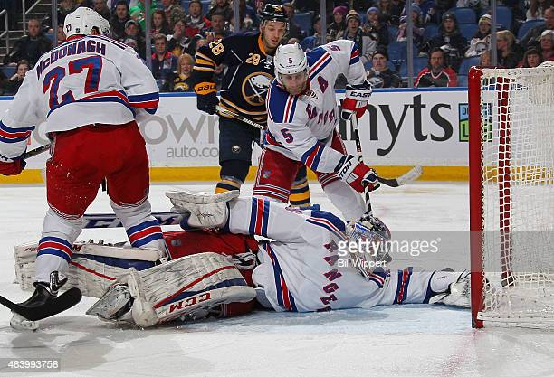 Mackenzie Skapski and Dan Girardi of the New York Rangers look for the puck during a scramble against the Buffalo Sabres on February 20 2015 at the...