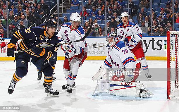 Mackenzie Skapski of the New York Rangers and Marcus Foligno of the Buffalo Sabres follow the puck on March 14 2015 at the First Niagara Center in...