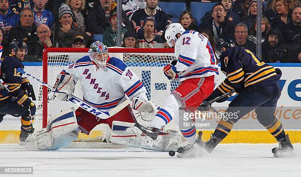 Mackenzie Skapski of the New York Rangers keeps a close eye on the puck as teammate Lee Stempniak defends Torrey Mitchell of the Buffalo Sabres on...