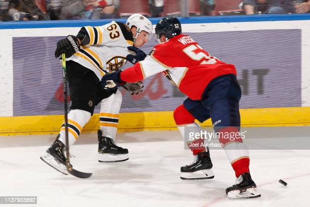 Mackenzie Weegar of the Florida Panthers checks Brad Marchand of the Boston Bruins off the puck during third period action at the BBT Center on March...