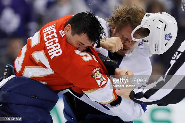 MacKenzie Weegar of the Florida Panthers fights Kasperi Kapanen of the Toronto Maple Leafs during the first period at BBT Center on February 27 2020...