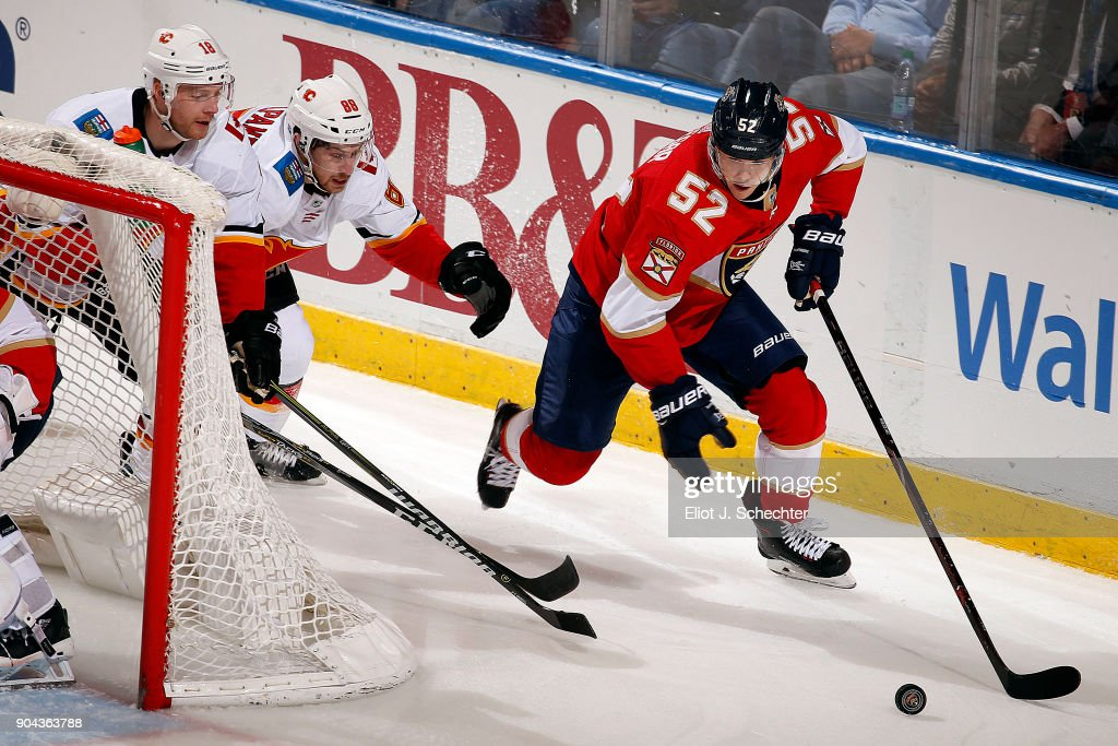 MacKenzie Weegar #52 of the Florida Panthers skates for possession against Matt Stajan #18 and Andrew Mangiapane #88 of the Calgary Flames at the BB&T Center on January 12, 2018 in Sunrise, Florida.