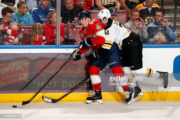 MacKenzie Weegar of the Florida Panthers tangles with Jake DeBrusk of the Boston Bruins at the BBT Center on March 23 2019 in Sunrise Florida