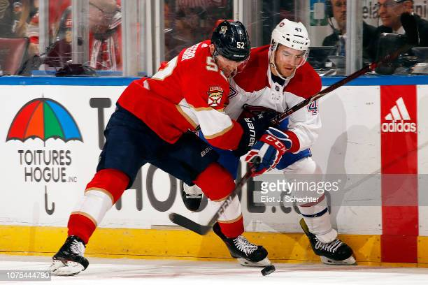MacKenzie Weegar of the Florida Panthers tangles with Kenny Agostino of the Montreal Canadiens at the BBT Center on December 28 2018 in Sunrise...
