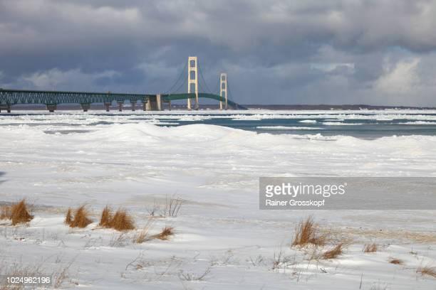 mackinac bridge crossing mackinac straits in winter - rainer grosskopf stock pictures, royalty-free photos & images