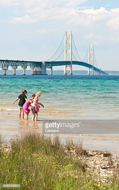 mackinac bridge with children playing on the water's edge - mackinac island stock pictures, royalty-free photos & images