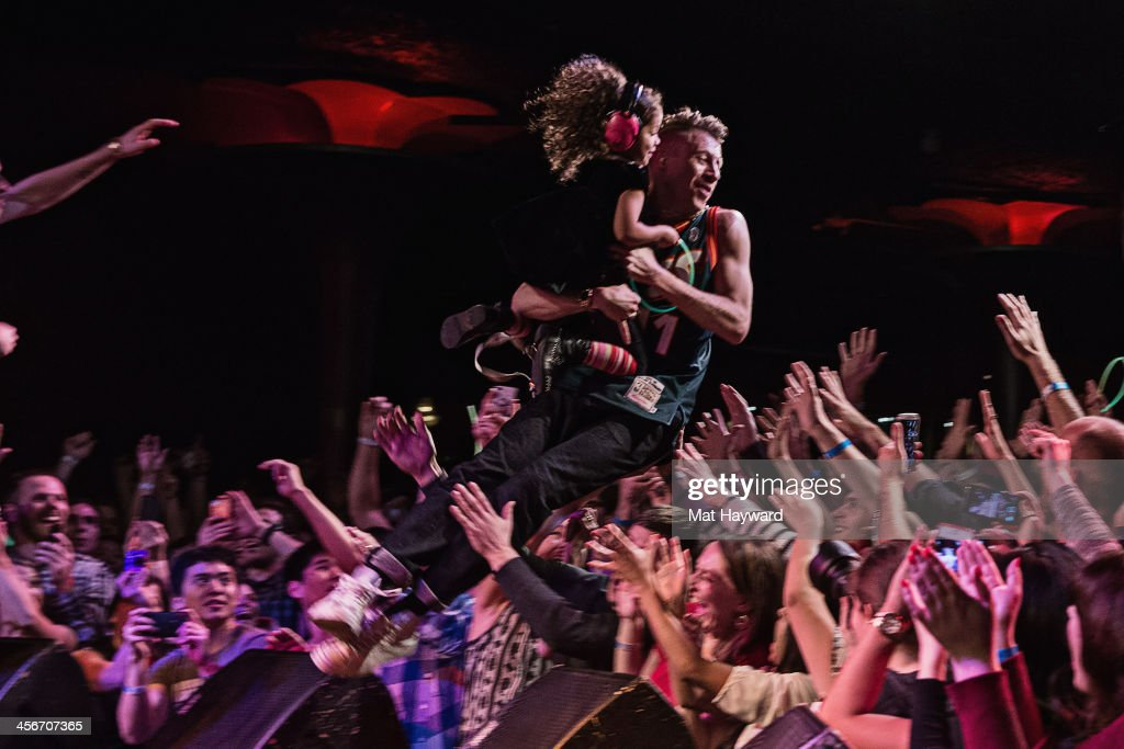 Macklemore stage dives with a small child while performing for (SMooCH) Seattle Musicians for Childrens Hospital Benefit at The Showbox Market on December 14, 2013 in Seattle, Washington.