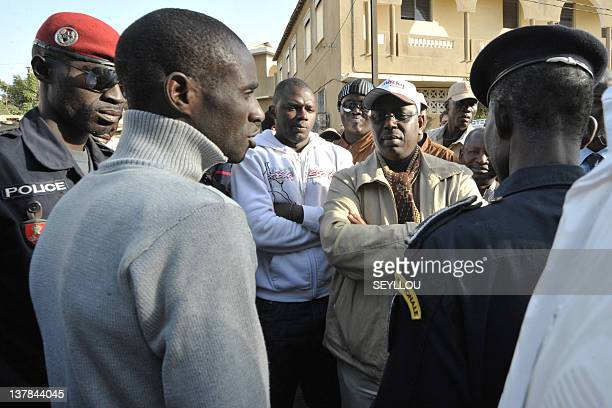 Macky Sall one of the leaders of the opposition 'Mouvement du 23 Juin' stands with other members of the opposition next to riot policemen blocking a...