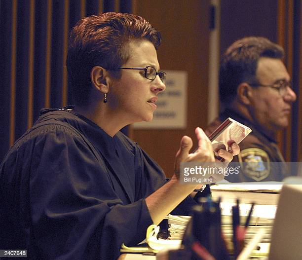 Macomb County Circuit Court Judge Deborah Servitto examines a rap CD that was handed to her by Marshall Mathers attorney Pete Peacock August 18 2003...