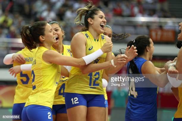 Macris Carneiro #4 Ana Carolina Silva #12 Natalia Pereira and team mates of Brazil celebrate winning the semi final match between Brazil and Serbia...