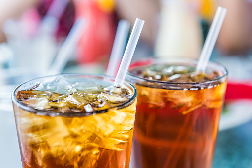 Macro closeup of iced tea or soda with ice cubes and straw in glass 900209858