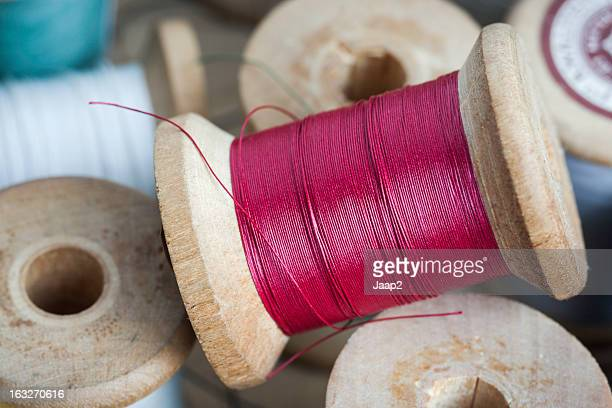 Macro close-up of red sewing thread on vintage wooden spool