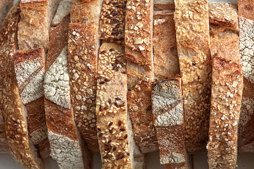 Macro photo of different pieces of fresh bread with flax seeds and sesame seeds. Healthy food. Flat lay 1054923162