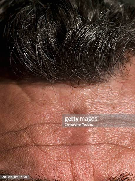 macro shot of senior man's forehead and hair - black hair stock pictures, royalty-free photos & images