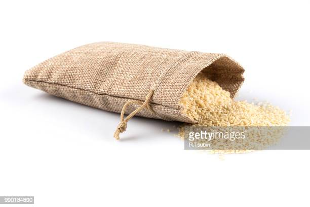 macro view of sesame seeds in flax sack with tie isolated on white background - sesame stock pictures, royalty-free photos & images