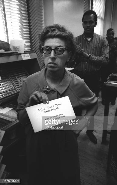 Macy's Department Store tag maker stands in front of a Linotype Machine and showing one of her labels in 1967 in New York City New York